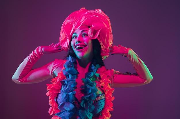 Schoonheid. hawaiiaans brunette model op paarse muur in neonlicht. mooie vrouwen in traditionele kleding glimlachen, dansen en plezier hebben. heldere feestdagen, feestkleuren, festival.