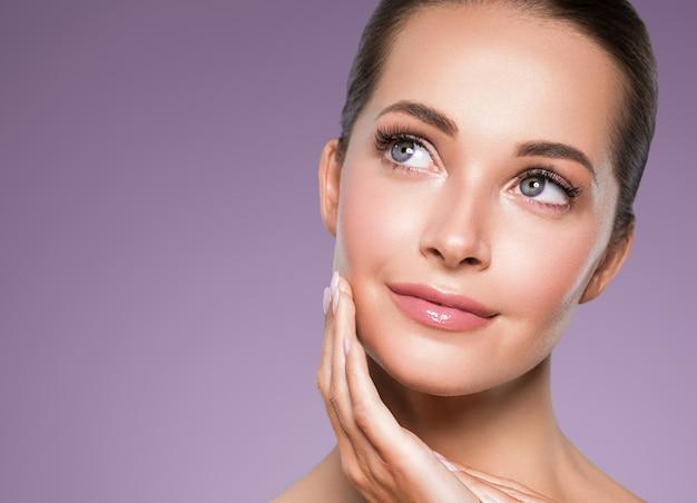 Schoonheid huid vrouw gezicht close-up gezond haar cosmetische natuurlijke make-up gelukkig model manicure nagels hand