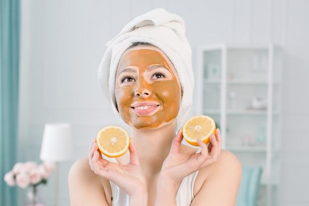 Schoonheid huidverzorging concept. aantrekkelijke blanke vrouw in witte handdoek met bruine gezichtsmasker op het gezicht houdt citrusvruchten op haar hand op lichte ruimte. spa-procedures en crème masker op de huid