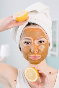 Schoonheid huidverzorging concept. vrij blanke vrouw in witte handdoek met bruine modder gezichtsmasker op het gezicht houdt citrusvruchten op haar hand op lichte ruimte. spa-procedures en masker op de huid