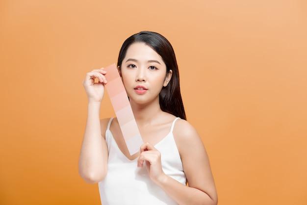 Schoonheid huidverzorgingsvrouw die huidskleurpapier toont, met een schone gezichtshuid, concept voor huidverzorging, aziatisch