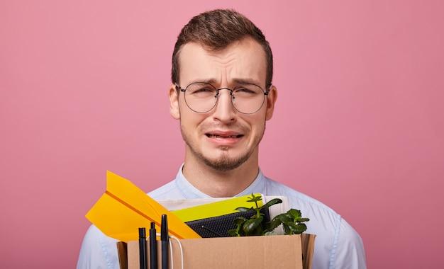 Schoonheid huilende man in een shirt en een bril heeft een kartonnen doos met pennen, planten en papieren vliegtuigje