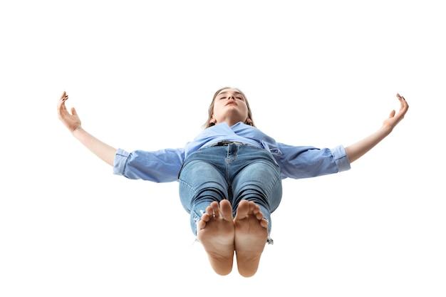 Schoonheid in de lucht greep in een oogwenk. volledige opname van een aantrekkelijke jonge vrouw die in de lucht zweeft en de ogen gesloten houdt. zweven in vrije val, gebrek aan zwaartekracht. vrijheid, emoties, kunstwerkconcept.