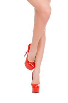 Schoonheid in schoenen met hoge hakken. close-up van mooie vrouw in rode schoenen met hoge hakken die zich voordeed terwijl ze geïsoleerd op wit stond