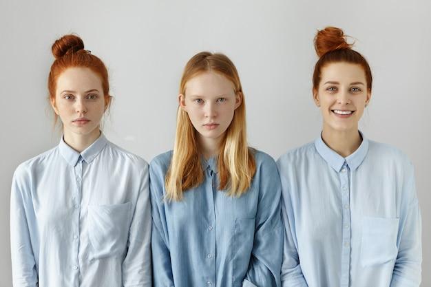 Schoonheid, jeugd, mensen en lifestyle. drie aantrekkelijke vriendinnen gekleed in soortgelijke blauwe shirts poseren