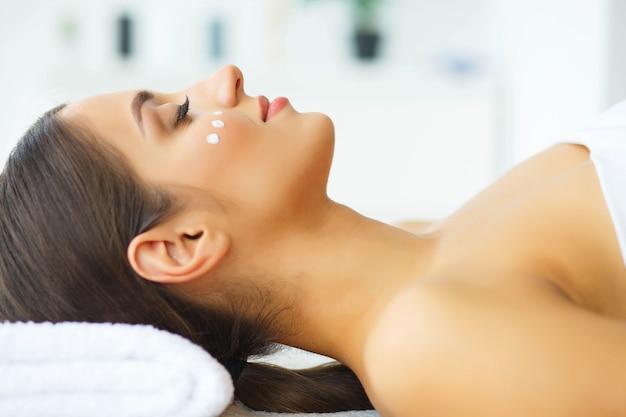 Schoonheid. jong meisje in schoonheidssalon. brunette vrouw met groene ogen. liggend op de massagetafels. schone en frisse huid. huidsverzorging. hoge resolutie