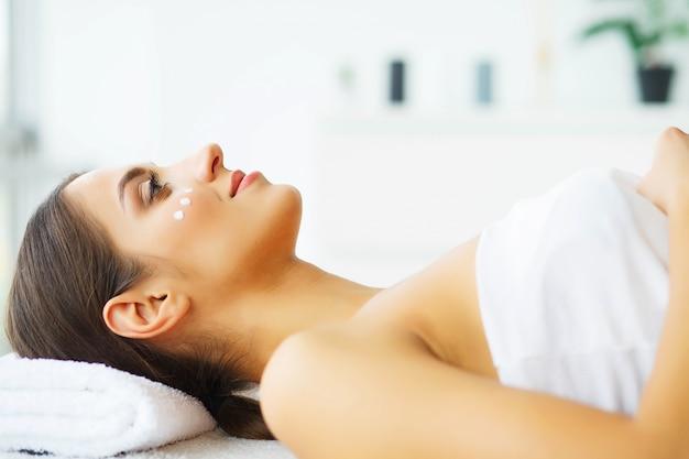 Schoonheid. jong meisje in schoonheidssalon. donkerbruine vrouw met groene ogen. liggend op de massagetafels. schone en frisse huid. huidsverzorging. hoge resolutie
