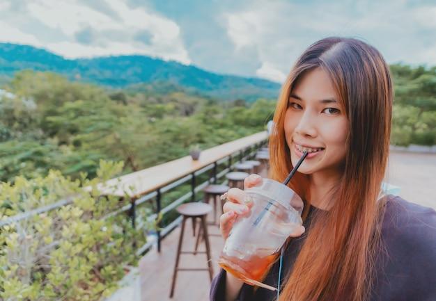 Schoonheid jonge aziatische glimlachende vrouw is in café met bos- en bergnatuurachtergrond terwijl ze ijskoude americano-koffie drinkt