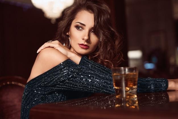 Schoonheid jonge brunette vrouw zitten aan de bar