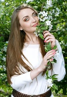 Schoonheid jonge vrouw in de appeltuin