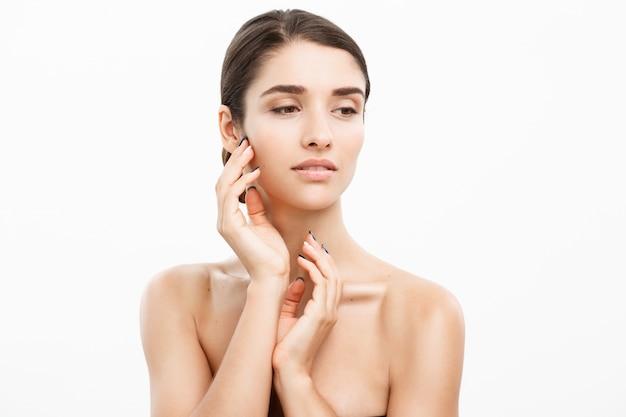 Schoonheid jonge vrouwelijke model meisje raakt haar gezicht huid wangen handen vingers