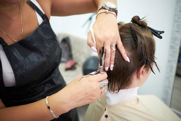 Schoonheid, kapsel, behandeling, haarverzorgingconcept. jonge stijlvolle vrouw bij de kapsalon. haarstylist serveren cliënt bij kapper of schoonheidssalon.