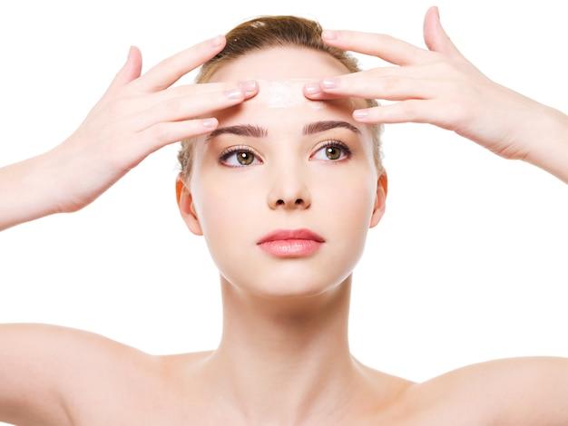 Schoonheid kaukasische jonge vrouw moisturizer crème op het voorhoofd toe te passen - geïsoleerd op wit