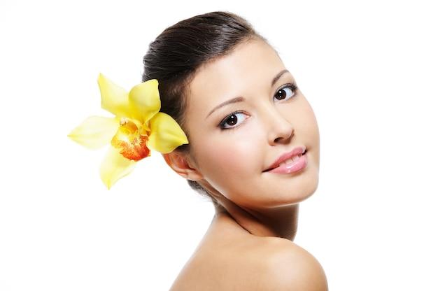 Schoonheid lachend vrouwelijk gezicht met gele orchidee uit haar oor - over wit