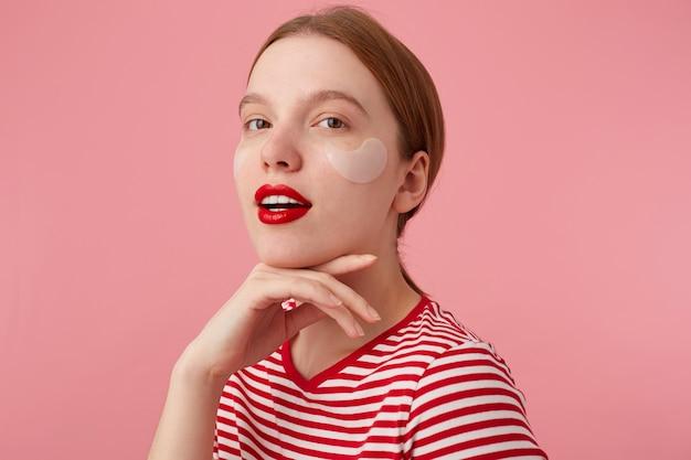 Schoonheid lachende roodharige dame draagt in een rood gestreept t-shirt, met rode lippen en met vlekken onder de ogen, raakt de kin, staat en geniet van vrije tijd voor huidverzorging.