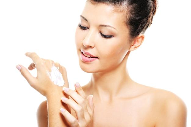 Schoonheid lachende vrouw cosmetische crème toe te passen op haar handen - over witte ruimte