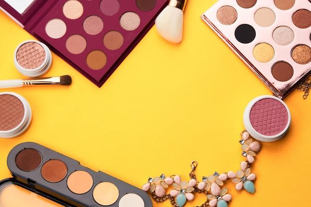 Schoonheid lay-out op een gekleurde achtergrond met cosmetica en sieraden