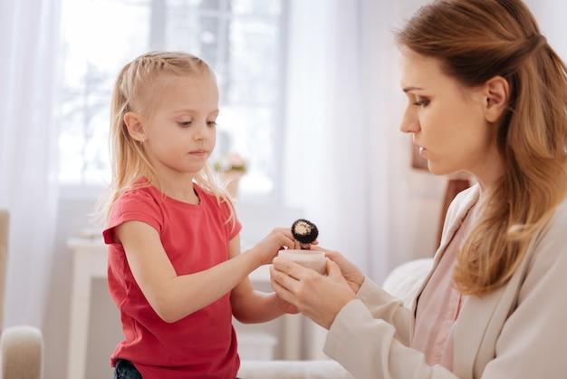 Schoonheid les. mooi jong blond meisje dat een make-upborstel vasthoudt en ernaar kijkt terwijl ze een schoonheidsles heeft met haar moeder