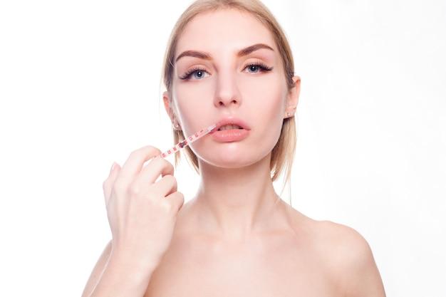 Schoonheid, make-up en mensen concept - aantrekkelijke jonge vrouw krijgt cosmetische injectie, geïsoleerd op wit oppervlak