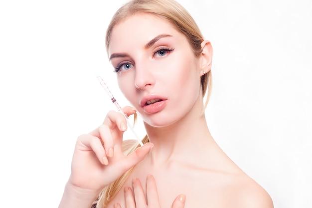 Schoonheid, make-up en mensen concept - aantrekkelijke jonge vrouw krijgt cosmetische injectie, geïsoleerd op witte achtergrond. artsenhanden die een injectie in gezicht maken. schoonheidsbehandeling.
