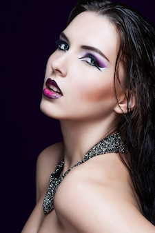 Schoonheid make-up. paarse make-up en kleurrijke heldere nagels