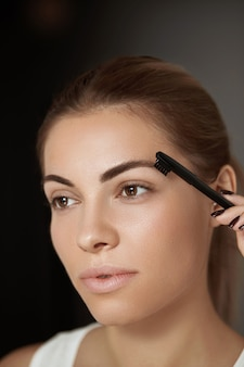 Schoonheid make-up. wenkbrauwen verzorging en make-up. portret van een mooi vrouwenmodel dat bruine wenkbrauwen vormgeeft.