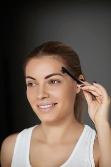 Schoonheid make-up. wenkbrauwen verzorging. mooie vrouw die wenkbrauwen met kam vormt. wenkbrauwen corrigeren en contouren.