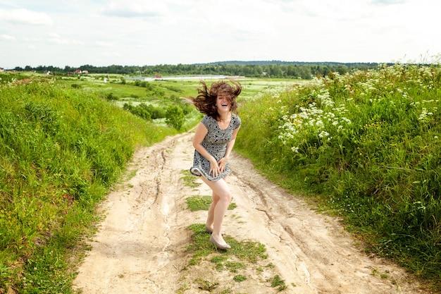 Schoonheid meisje buiten genieten van de natuur op zomer veld met bloeiende wilde bloemen