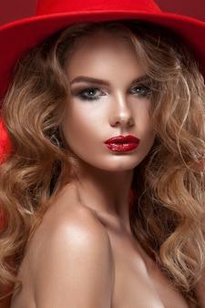 Schoonheid meisje in een rode kerstmuts en fir tree in handen. schone huid, lichte make-up, rode lippenstift, rode haarkleur