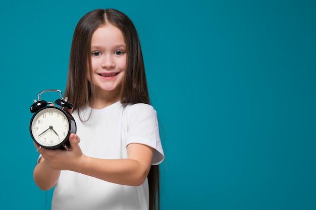 Schoonheid meisje in t-shirt met lang haar houdt de klok vast
