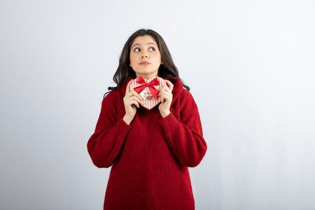 Schoonheid meisje met hartvormige geschenkdoos wegkijken.
