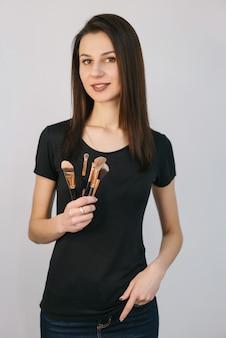 Schoonheid meisje met make-up borstels. make-up aanbrengen. de mooie jonge vrouw die verschillend houdt maakt omhoog borstels