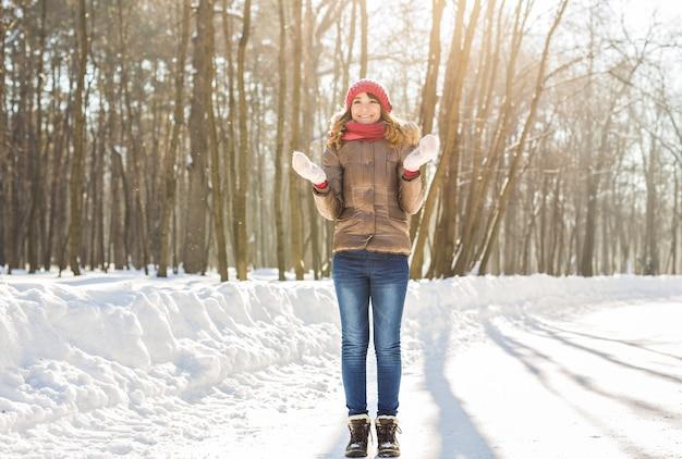 Schoonheid meisje waait sneeuw in ijzig winter park. buitenshuis. vliegende sneeuwvlokken.
