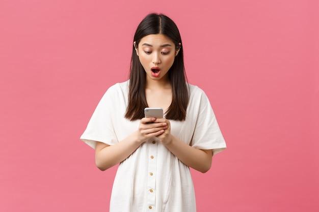 Schoonheid, mensen emoties en technologie concept. geschokt en geschrokken aziatisch meisje dat groot nieuws op mobiele telefoon leest, staren naar het smartphonescherm verbaasd met neergelaten kaak, staande roze achtergrond.