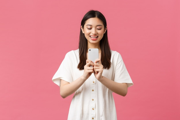 Schoonheid, mensen emoties en technologie concept. glimlachende gelukkige aziatische vrouwelijke blogger, stijlvol meisje dat foto's maakt op smartphone, er vrolijk uitziet als fotograferen, een foto maakt met mobiele telefoon.