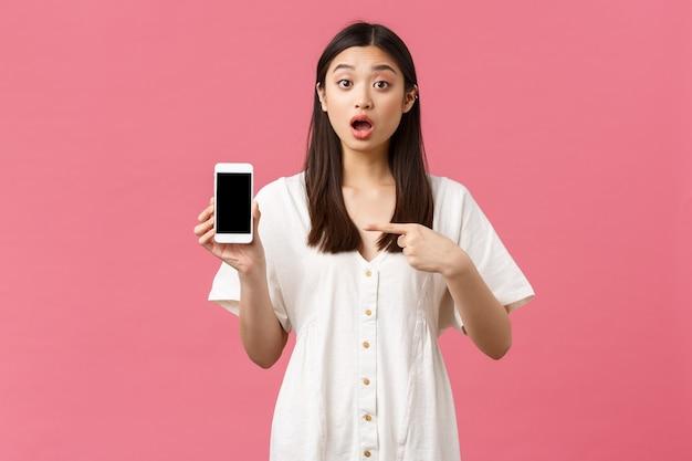 Schoonheid, mensen emoties en technologie concept. vrij stijlvol koreaans meisje die toepassing op het smartphonescherm toont. vrouw kijkt geschokt als ze groot nieuws vertelt en wijst naar de app voor mobiele telefoons.