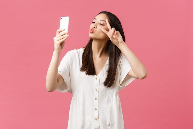 Schoonheid, mensen emoties en technologie concept. vrouwelijke knappe stijlvolle aziatische meisjesblogger die selfie op smartphonecamera neemt, gelukkig glimlacht op mobiele telefoon, staande roze achtergrond.