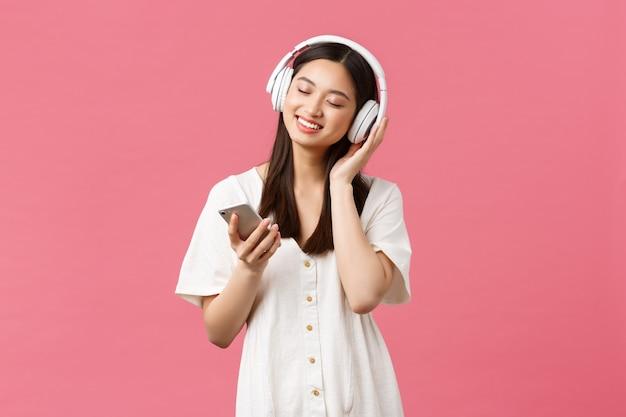 Schoonheid, mensen emoties en technologie concept. zorgeloos sensueel en mooi aziatisch meisje dat geniet van muziek in een draadloze koptelefoon, ogen dicht en glimlachend naar favoriete liedje luistert, smartphone vasthoudt