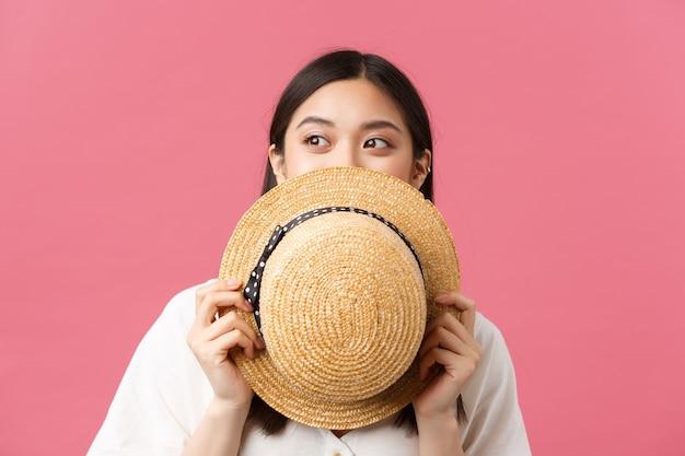 Schoonheid, mensen emoties en zomer vrije tijd concept. close-up van dromerig mooi aziatisch meisje dat gezicht achter strohoed verbergt en links naar promobanner gluurt, glimlachend met ogen, roze achtergrond