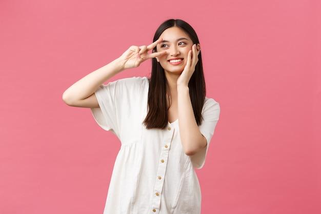 Schoonheid, mensen emoties en zomer vrije tijd concept. dromerig en romantisch schattig glimlachend aziatisch meisje dat bedachtzaam wegkijkt terwijl ze de zachte huid op het gezicht aanraakt en vredesteken toont, roze achtergrond