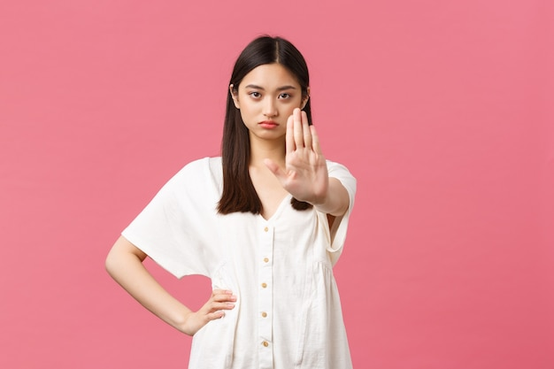 Schoonheid, mensen emoties en zomer vrije tijd concept. ernstige beu jonge aziatische vrouw zegt te stoppen, hand in verbod uit te breiden, waarschuwing te geven of toegang te beperken, roze achtergrond.