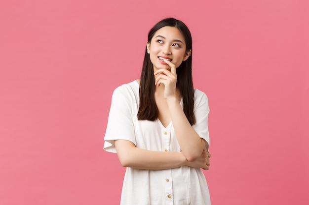 Schoonheid, mensen emoties en zomer vrije tijd concept. geïntrigeerd en attent, glimlachend aziatisch meisje dat van plan is, linksboven in de hoek kijkt en met een tevreden grijns denkt, idee heeft, roze achtergrond.