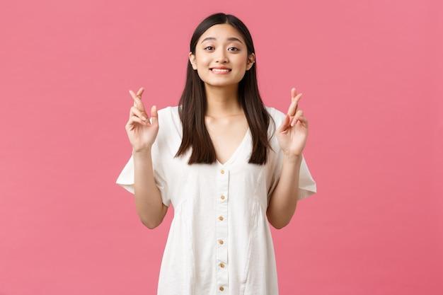 Schoonheid, mensen emoties en zomer vrije tijd concept. hoopvol dromerig kawaii aziatisch meisje in witte jurk die wens doet, kruis vingers veel geluk en starende camera, anticiperend op goed nieuws.