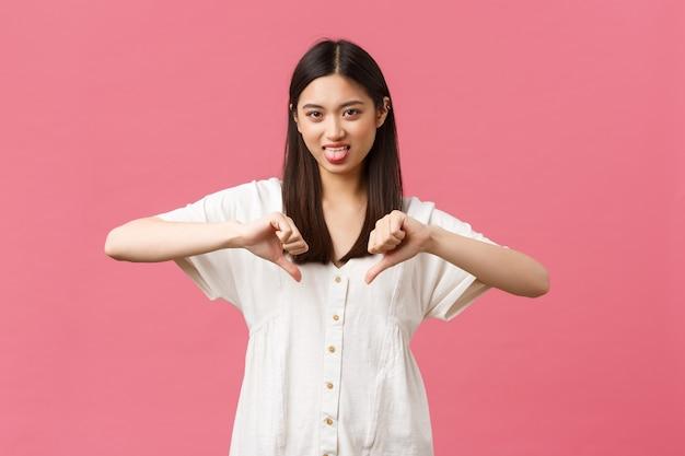 Schoonheid, mensen emoties en zomer vrije tijd concept. kieskeurig dwaas aziatisch meisje met slecht gedrag, tong van afkeer en duim omlaag, afschuwelijk walgelijk product beoordelend, roze achtergrond.