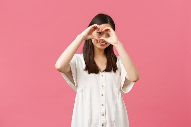 Schoonheid, mensen emoties en zomer vrije tijd concept. mooi, romantisch verlegen aziatisch meisje in witte jurk bekent sympathie of liefde, zoals iemand, toont een hartteken en glimlacht over roze achtergrond.