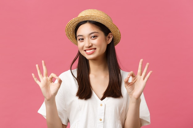 Schoonheid, mensen emoties en zomer vrije tijd en vakantie concept. glimlachend gelukkig aziatisch meisje in strohoed met goed gebaar, raad een perfect hotel of toeristenoord aan, staande roze achtergrond.