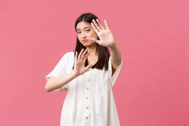 Schoonheid, mensen emoties en zomer vrije tijd en vakantie concept. somber en overstuur schattig aziatisch meisje dat vraagt om te stoppen met schieten, handen verdedigend op te steken, gezicht te bedekken van lichte, roze achtergrond.