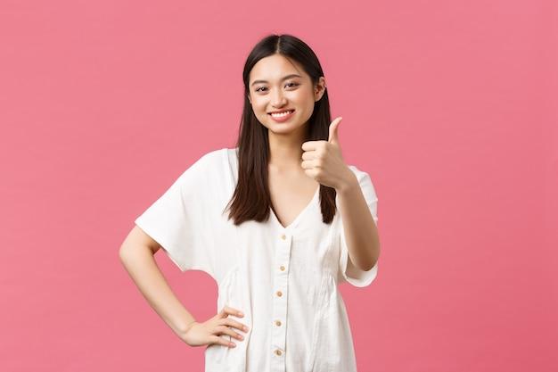 Schoonheid, mensen emoties en zomer vrije tijd en vakantie concept. tevreden schattig aziatisch meisje in witte jurk, duim omhoog in goedkeuring, leuk vinden en mee eens, uitstekend product beoordelen, roze achtergrond