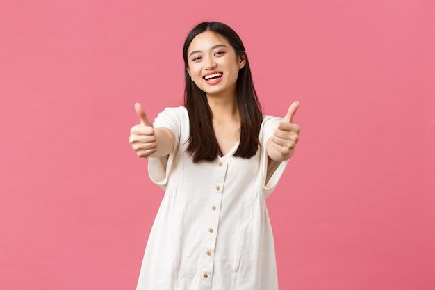Schoonheid, mensen emoties en zomer vrije tijd en vakantie concept. vriendelijk, vrolijk aziatisch meisje lacht en toont duimen, raad een geweldig hotel of kuuroord aan, roze achtergrond