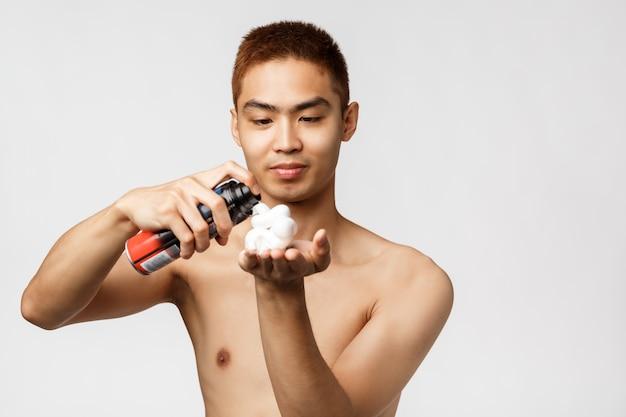 Schoonheid, mensen en hygiëne concept. het portret van de aziatische knappe mens met naakt torso wil varkenshaar scheren, glimlachend tevreden als gebruikscheercrème, bevindende witte muur